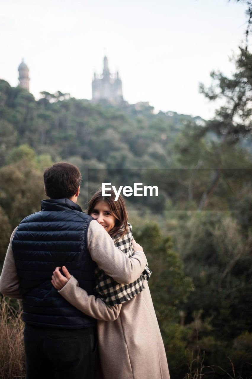 two people, women, positive emotion, togetherness, couple - relationship, love, tree, bonding, plant, emotion, focus on foreground, young adult, adult, men, standing, rear view, young women, heterosexual couple, nature, leisure activity, arm around, outdoors, hairstyle