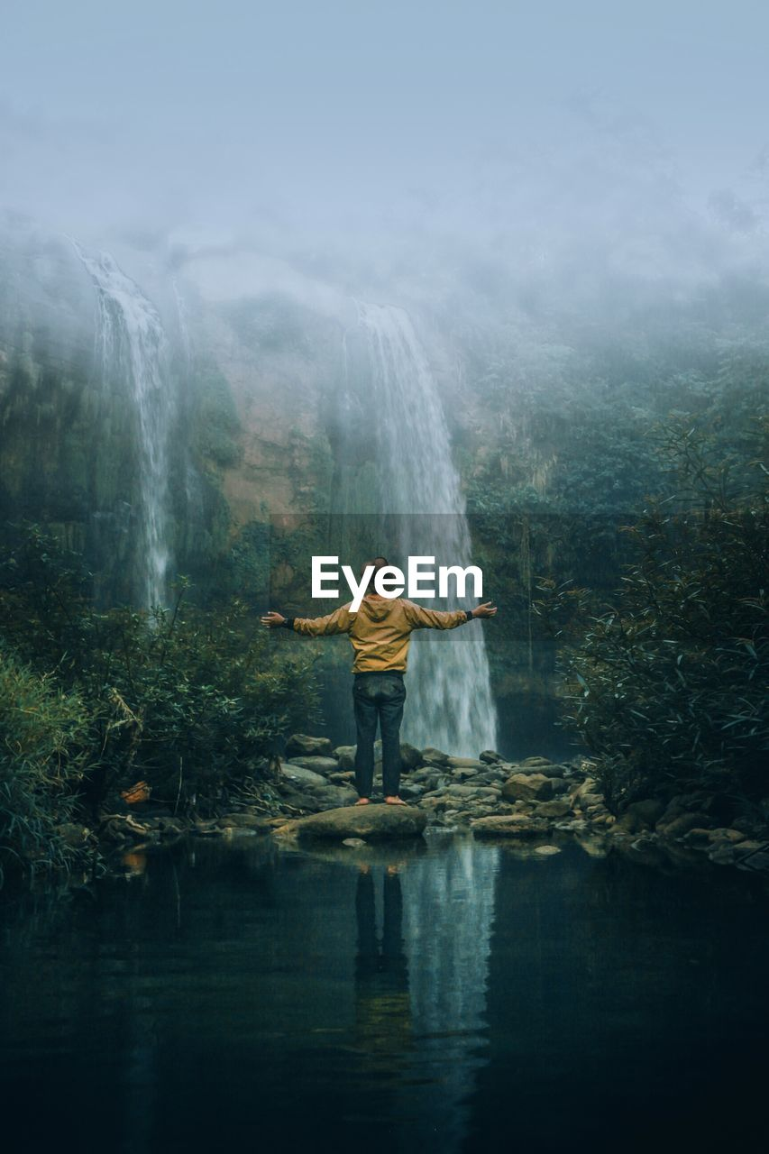 Man Standing Against Waterfall In Forest