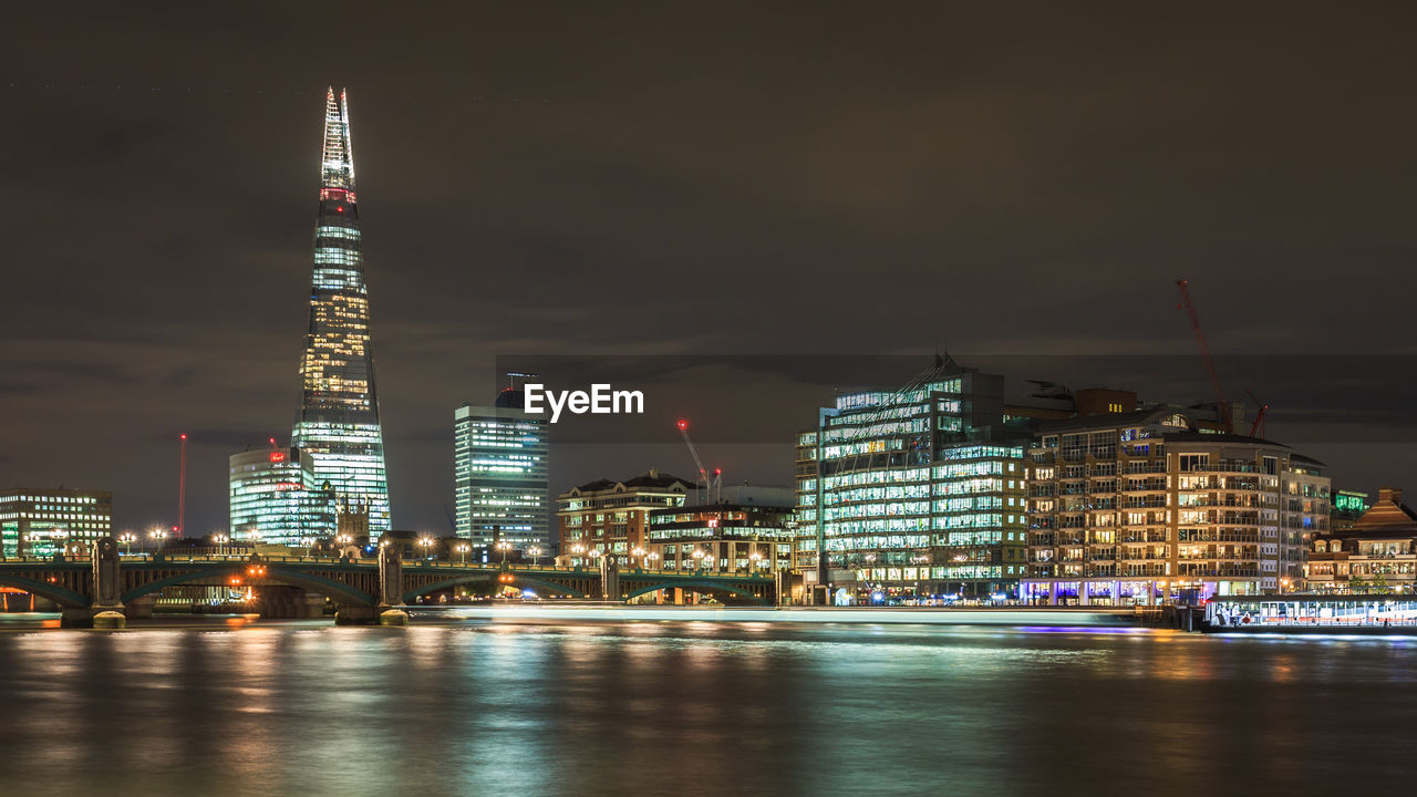 Shard london bridge by thames river against sky in illuminated city at night