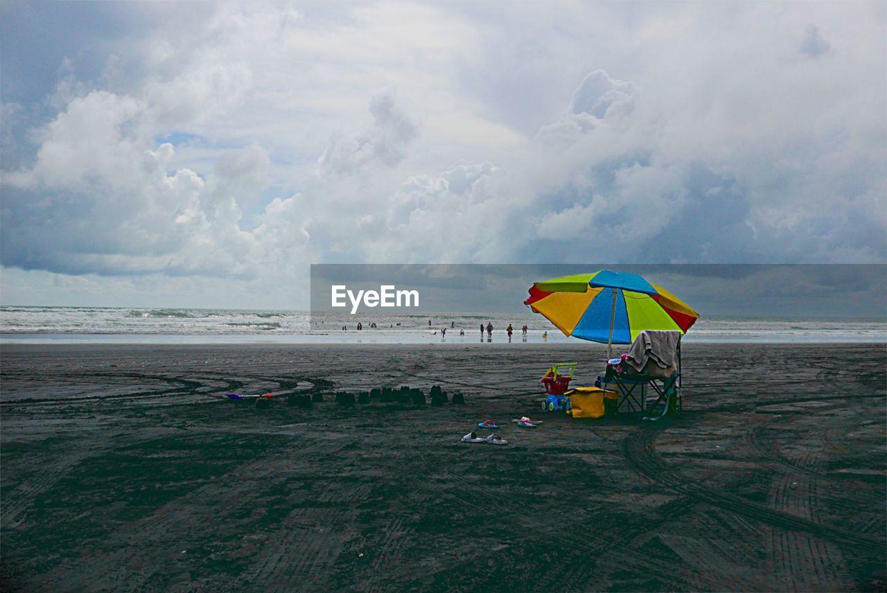 PEOPLE ON BEACH AGAINST SKY DURING RAIN