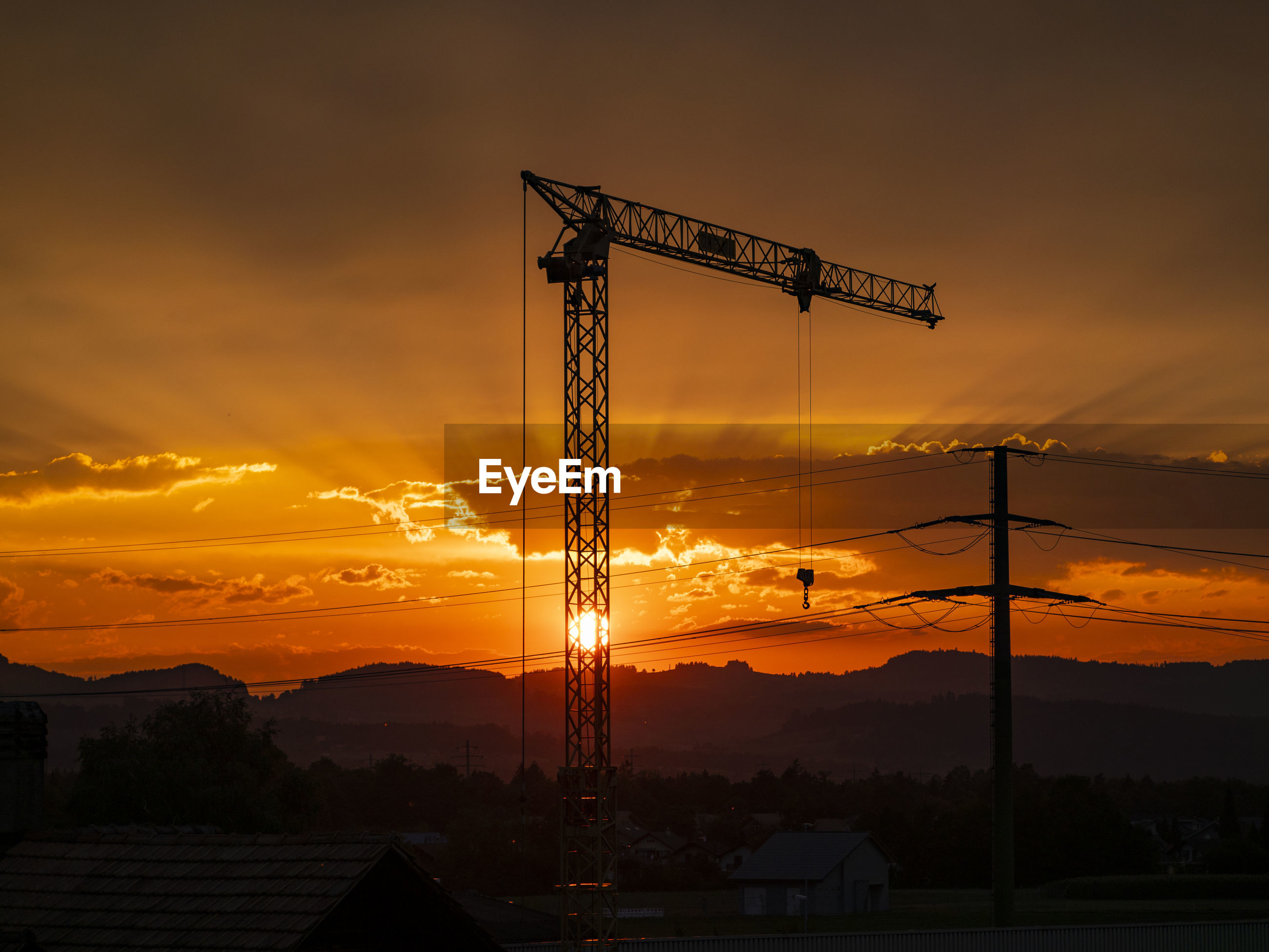 SILHOUETTE OF CRANE AT CONSTRUCTION SITE DURING SUNSET