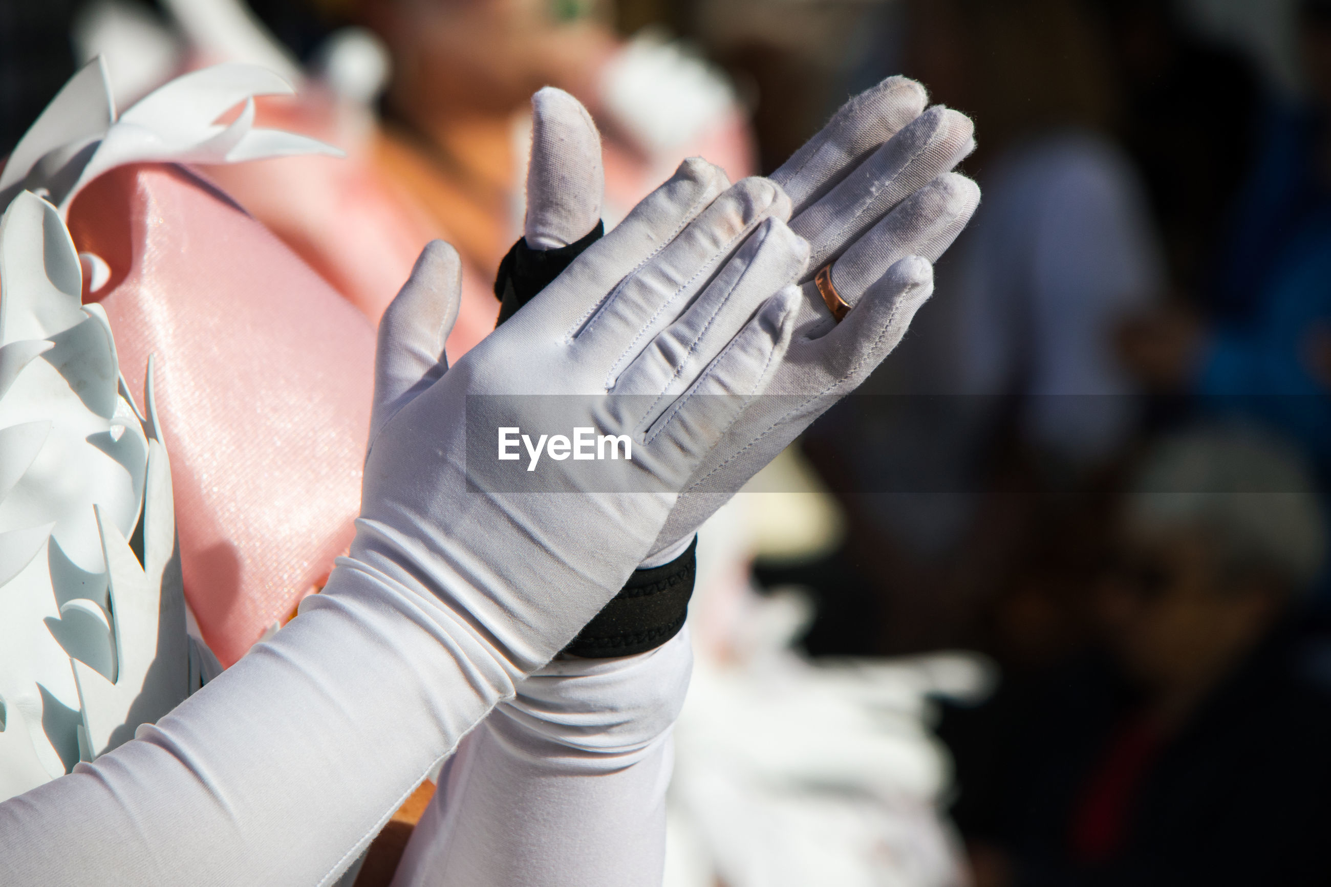 Close-up of hands with gloves applaud