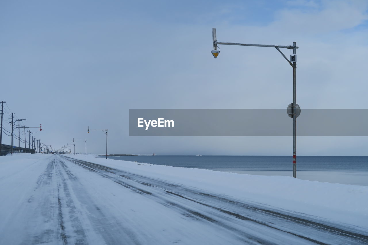 cold temperature, snow, winter, sky, nature, lighting equipment, transportation, street, road, direction, street light, no people, scenics - nature, beauty in nature, day, outdoors, covering, diminishing perspective, the way forward, light