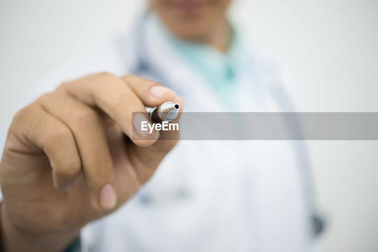 Midsection Of Doctor Holding Pen Over White Background