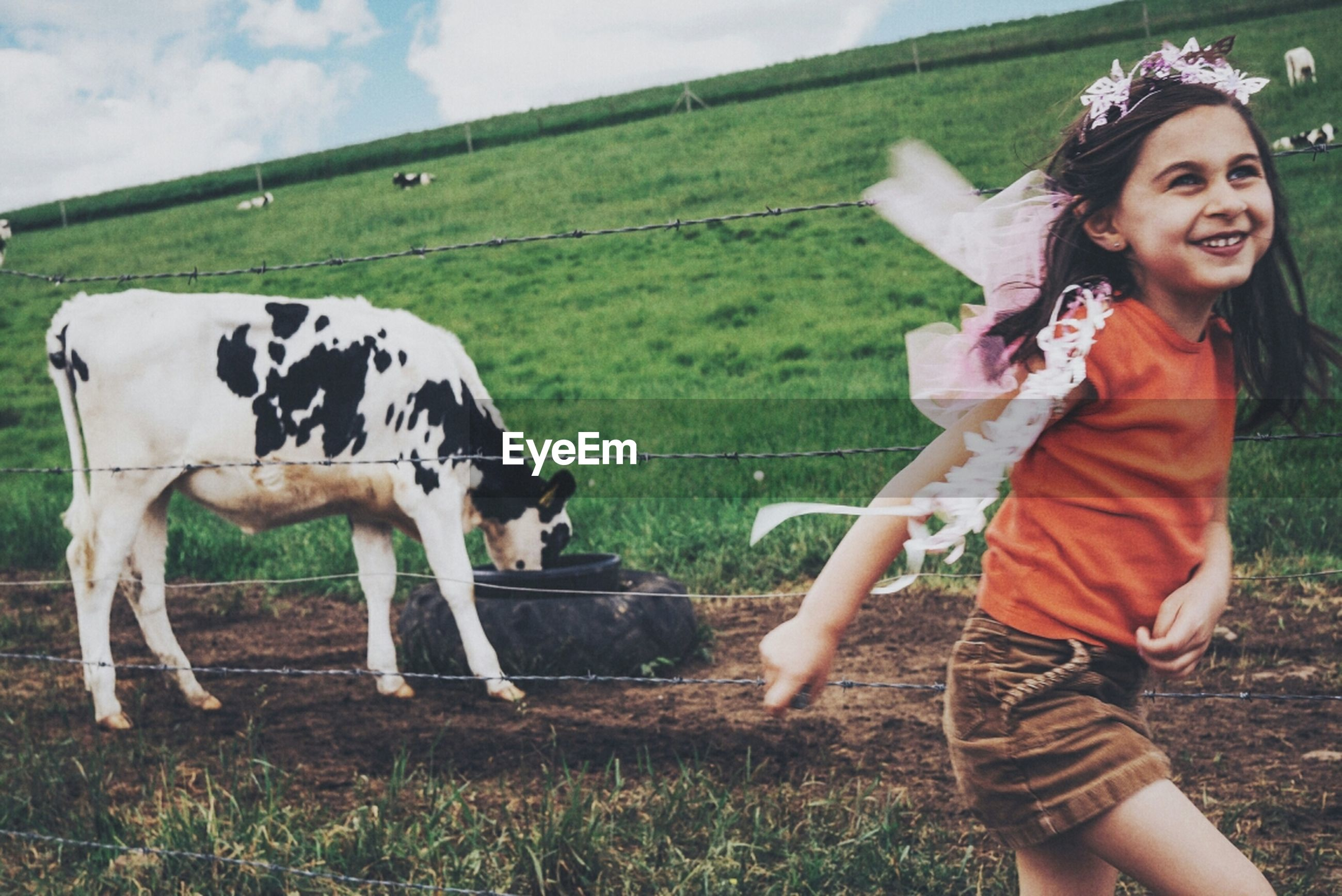 Side view of girl running on field against a cow