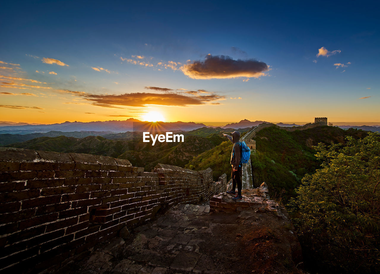 Man standing on great wall of china against cloudy sky during sunset
