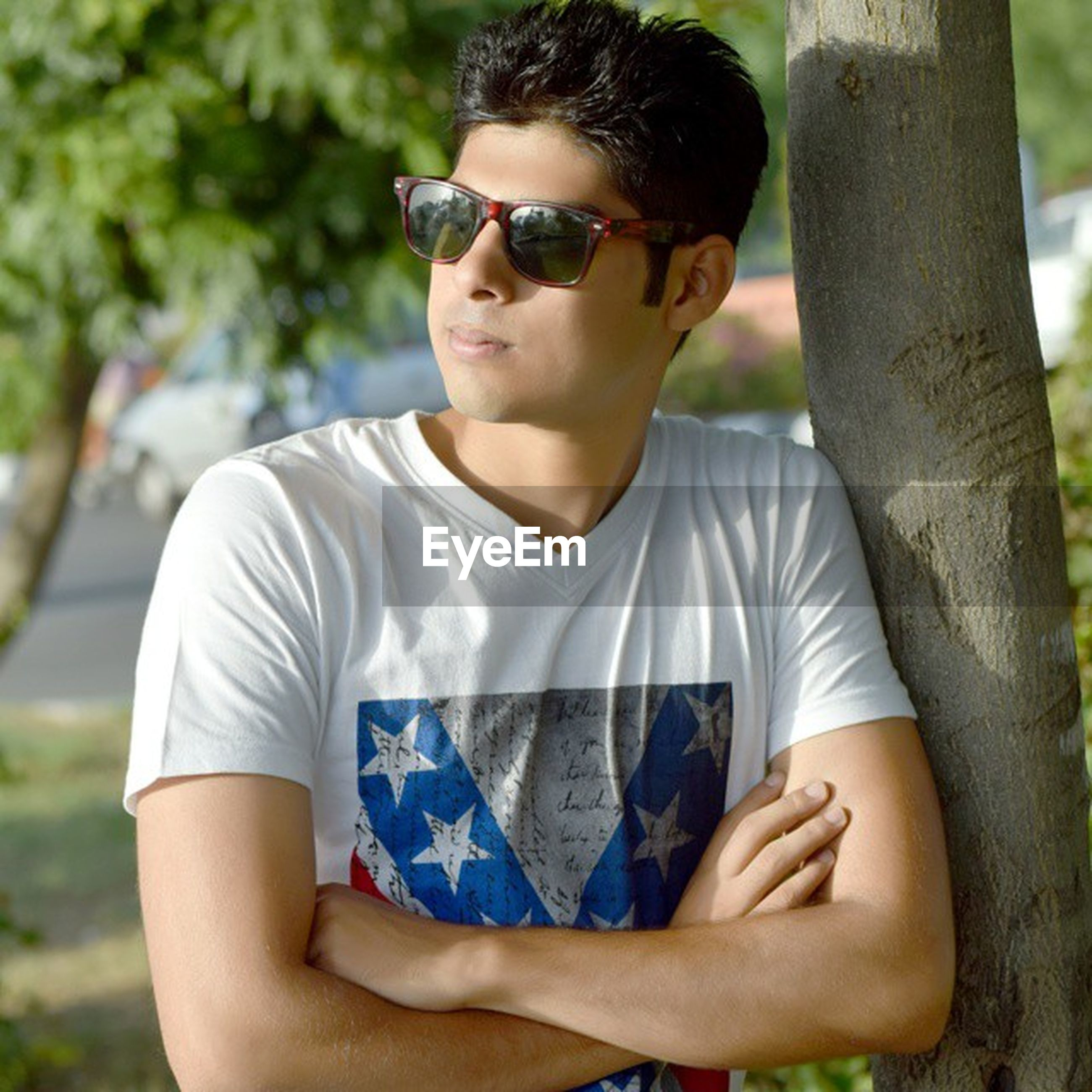 lifestyles, young adult, person, leisure activity, casual clothing, focus on foreground, front view, sunglasses, looking at camera, portrait, holding, waist up, young men, sitting, three quarter length, smiling