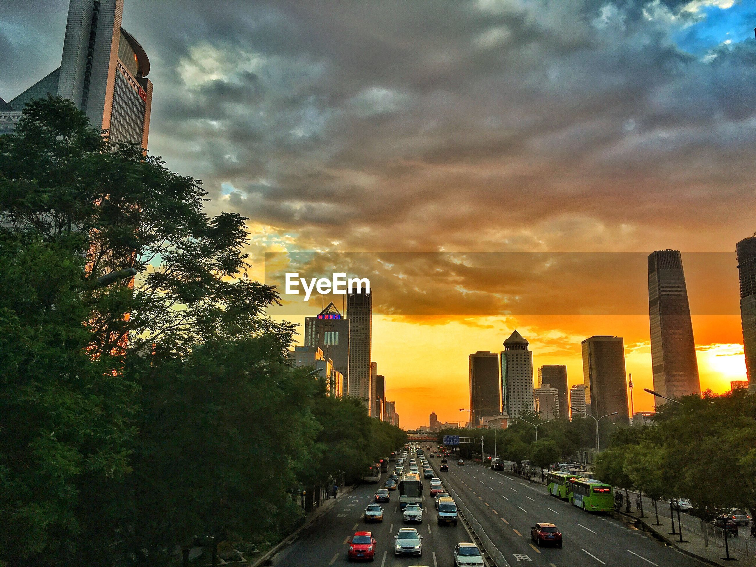 transportation, car, land vehicle, architecture, mode of transport, building exterior, built structure, city, sunset, road, sky, street, cloud - sky, traffic, the way forward, on the move, skyscraper, city life, tall - high, orange color