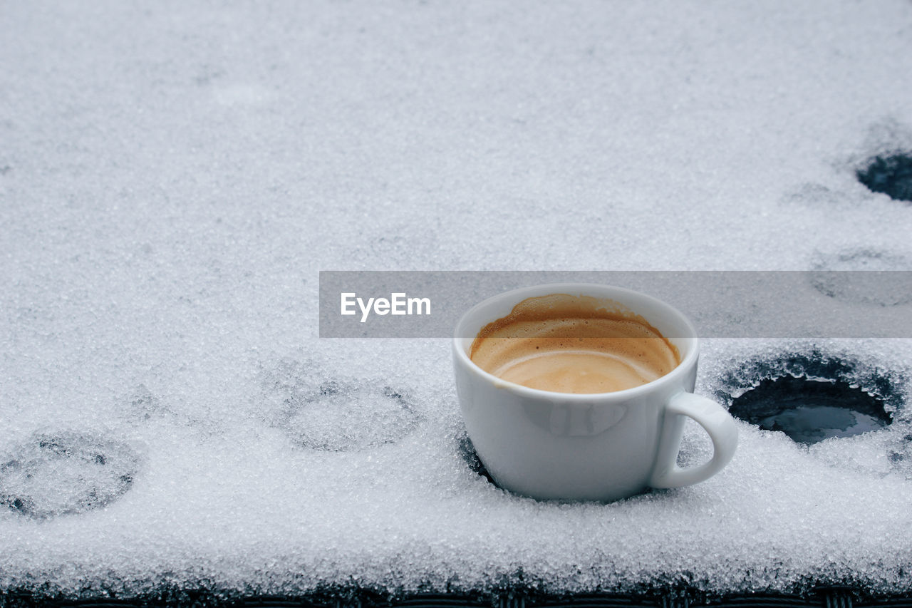 High angle view of coffee cup on snow