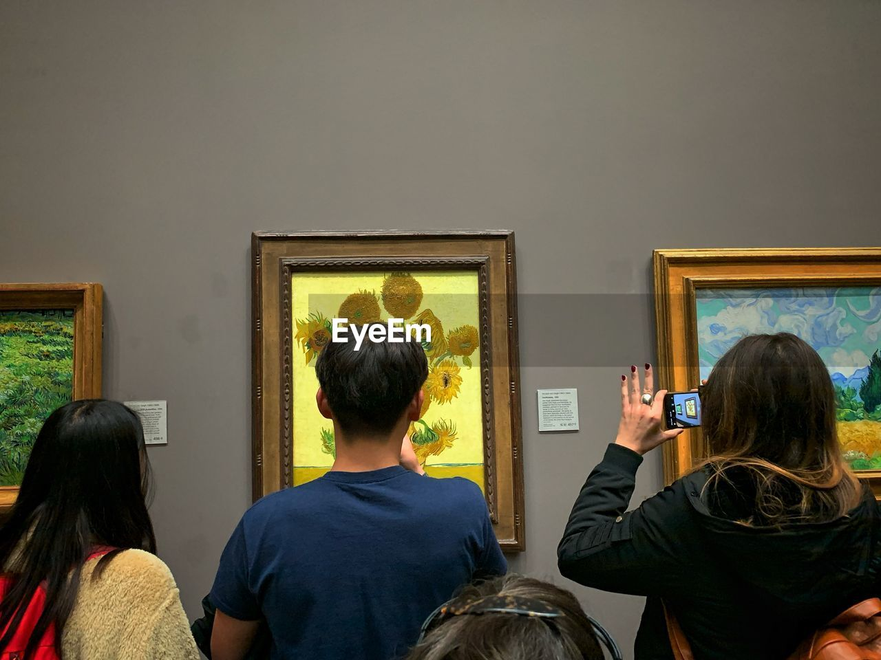 rear view, indoors, adult, men, real people, women, people, frame, headshot, lifestyles, picture frame, casual clothing, mirror, wall - building feature, art museum, group of people, technology, waist up, looking, portrait, hairstyle