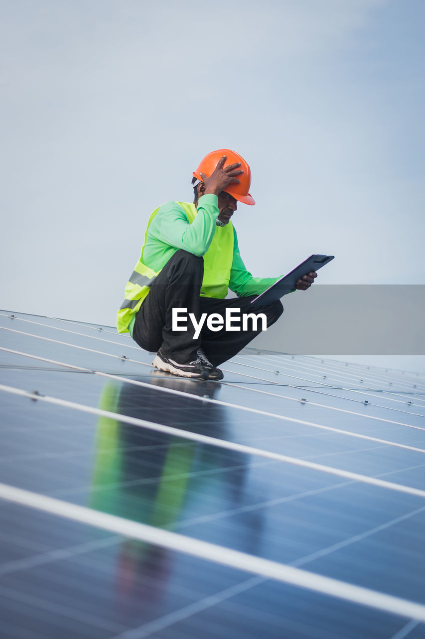environmental conservation, renewable energy, sky, solar panel, alternative energy, solar energy, full length, environment, real people, technology, one person, occupation, nature, men, fuel and power generation, side view, day, environmental issues, headwear