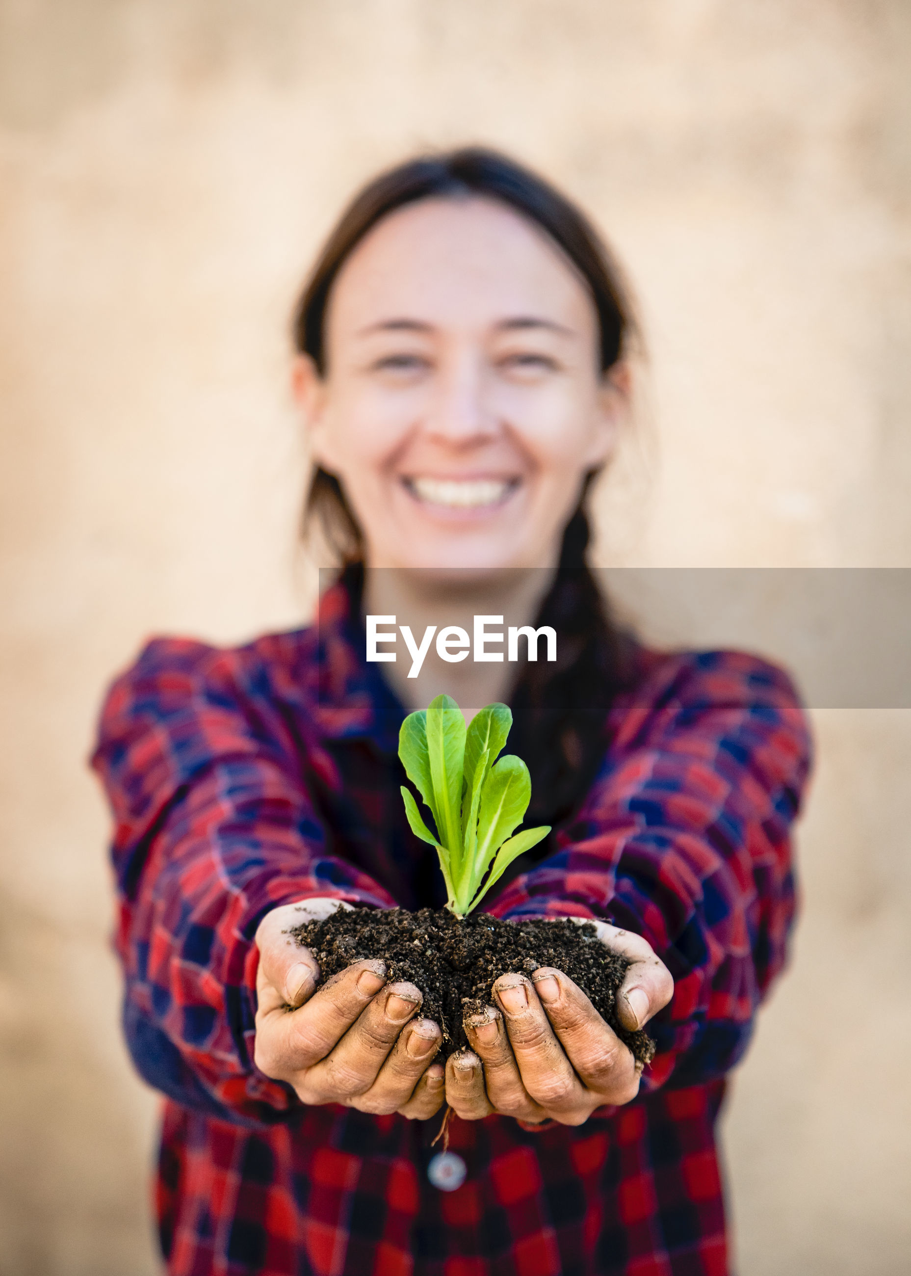 Portrait of smiling woman holding plant in soil