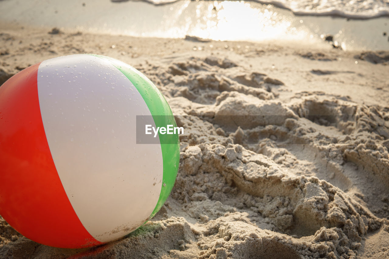 land, beach, sand, ball, focus on foreground, nature, close-up, sport, no people, sunlight, still life, day, outdoors, sphere, leisure activity, sports equipment, holiday, volleyball - sport, brown, summer