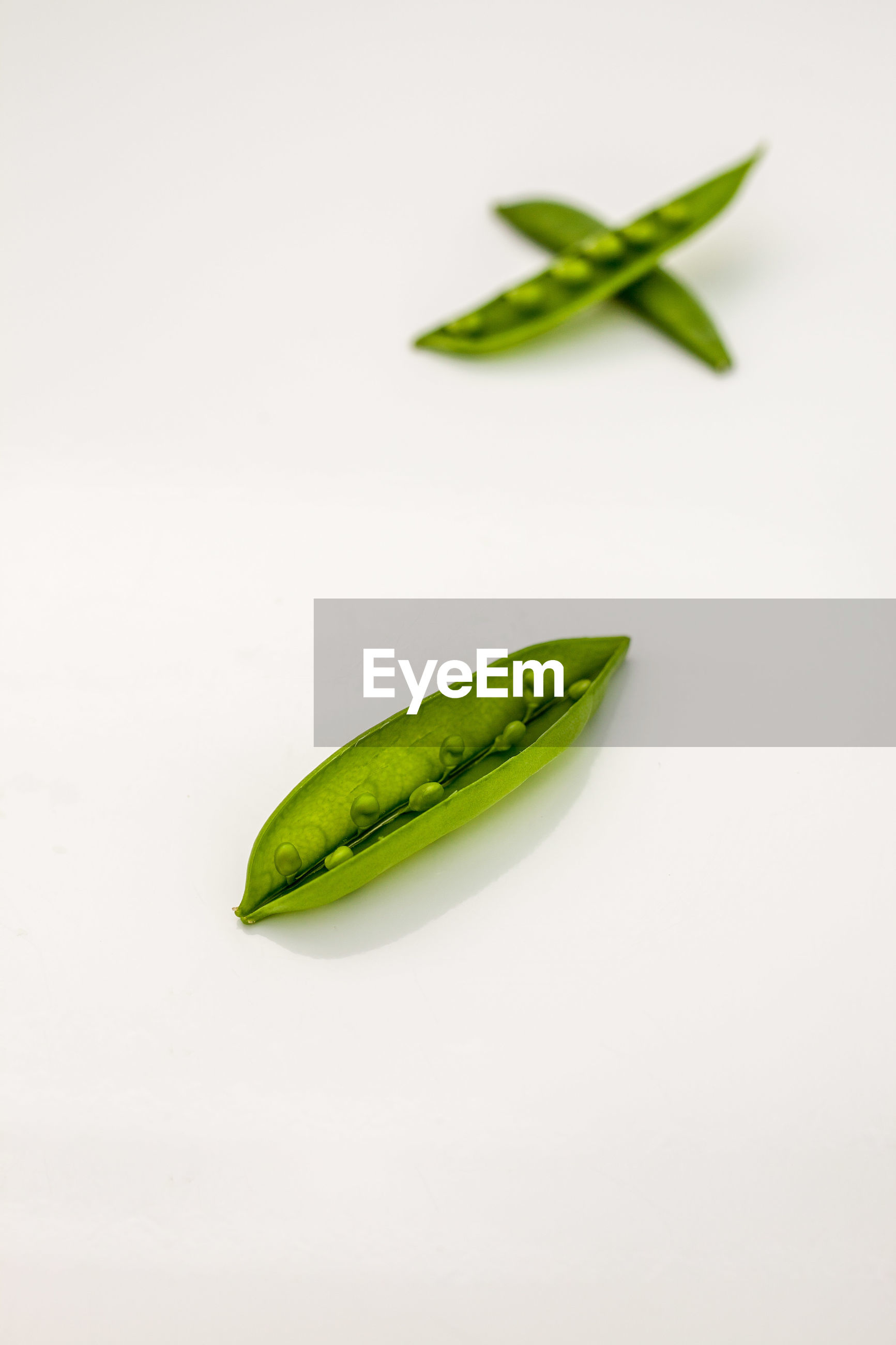 Close-up of green pea pods over white background