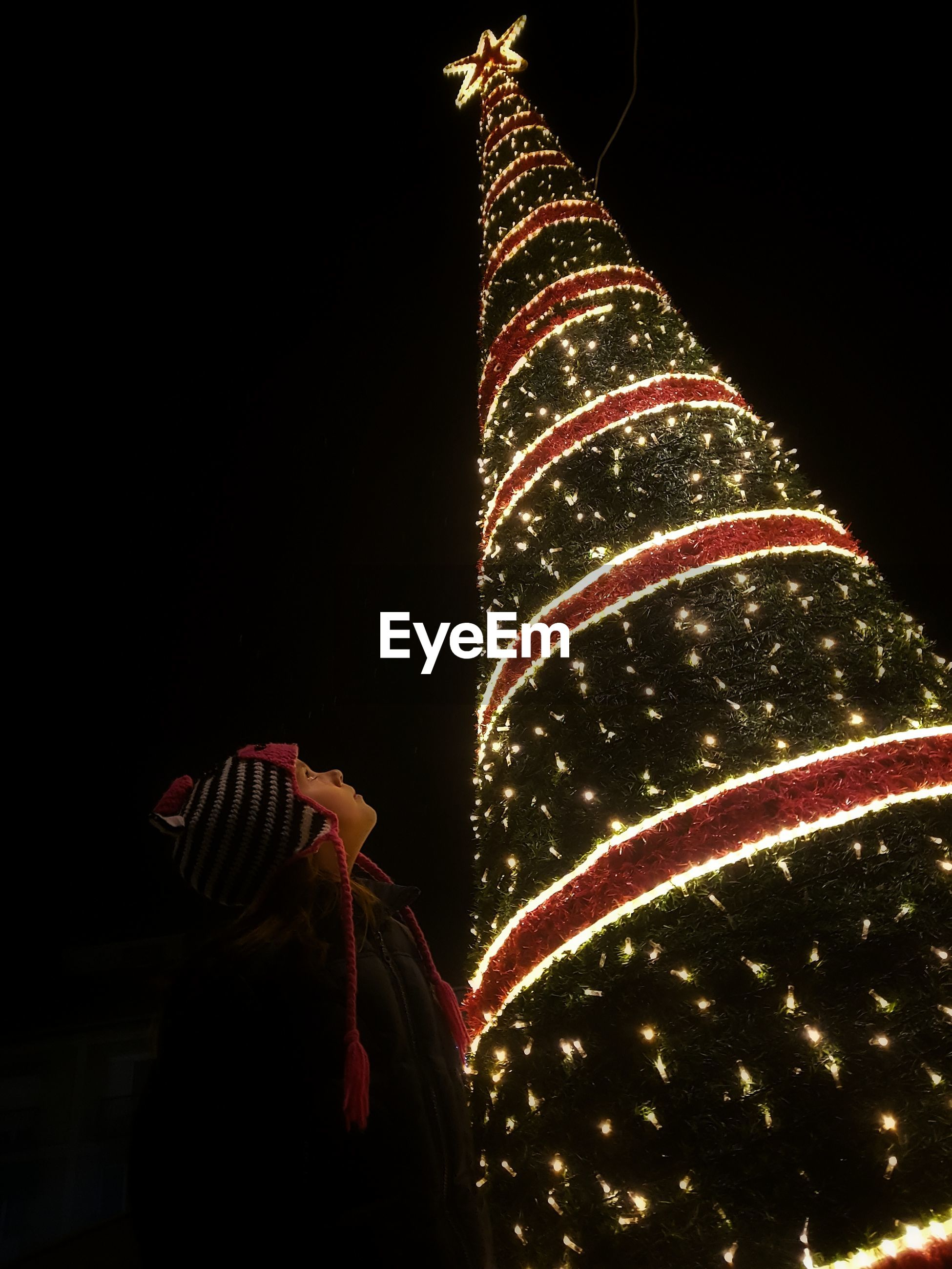 Low angle view of boy looking at illuminated christmas tree against sky during night