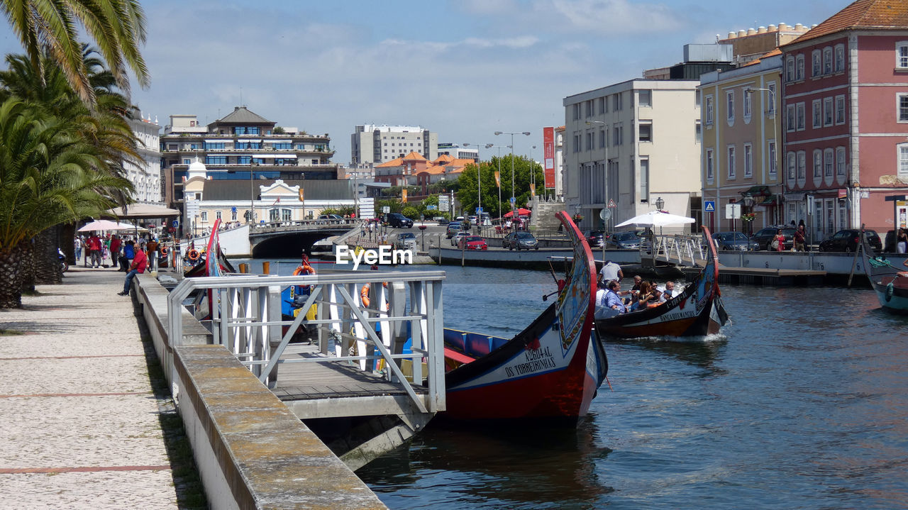 water, nautical vessel, transportation, building exterior, mode of transportation, architecture, built structure, city, nature, sky, incidental people, waterfront, day, moored, canal, building, sea, large group of people, residential district, outdoors, passenger craft