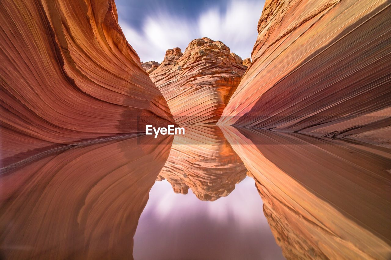 Rock Formations Reflecting On Calm Lake At Coyote Buttes