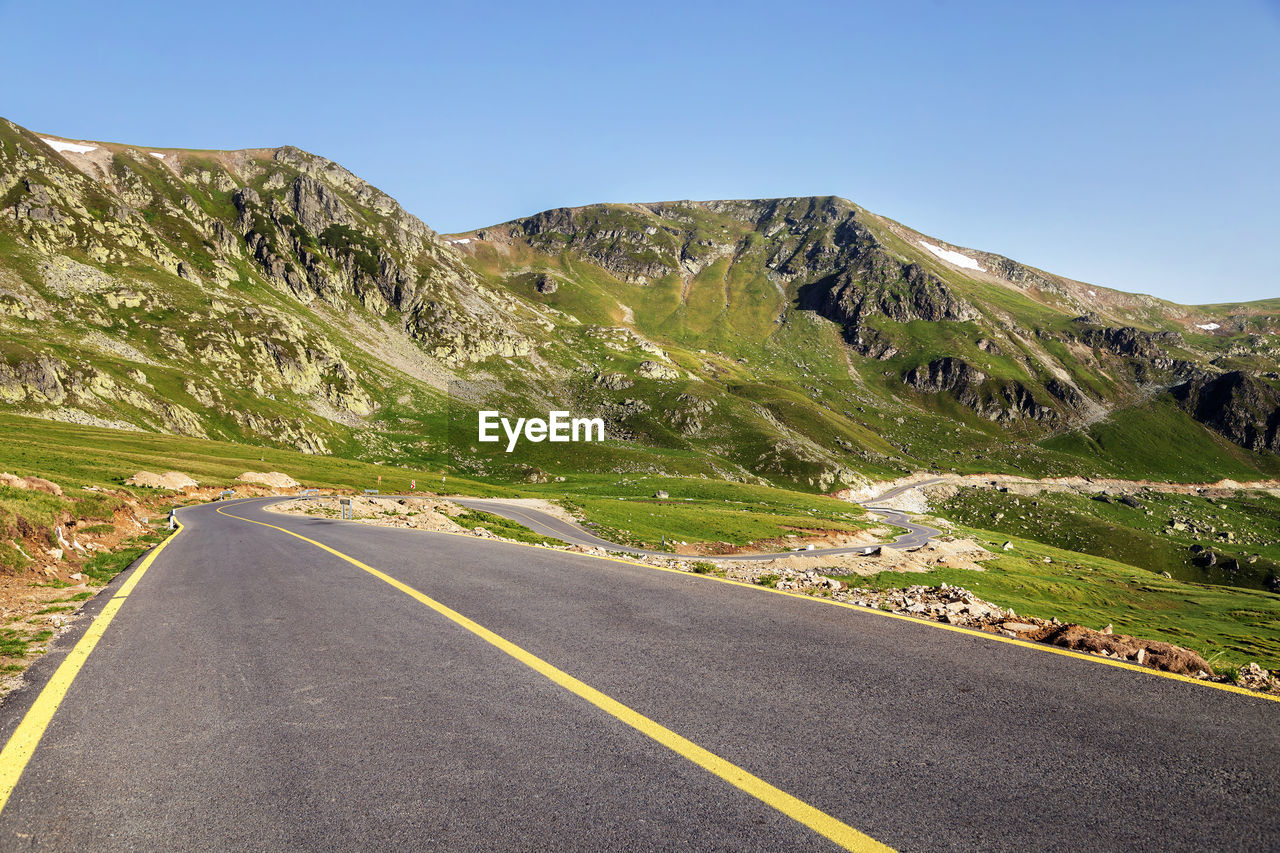 road, transportation, sky, direction, mountain, symbol, the way forward, road marking, marking, scenics - nature, sign, nature, diminishing perspective, beauty in nature, environment, landscape, non-urban scene, asphalt, empty road, clear sky, no people, mountain range, dividing line, outdoors