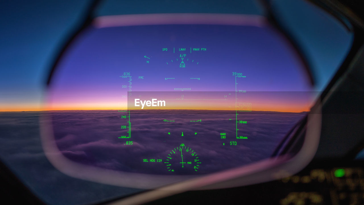 Boeing 787 cockpit window view at sunrise above the clouds