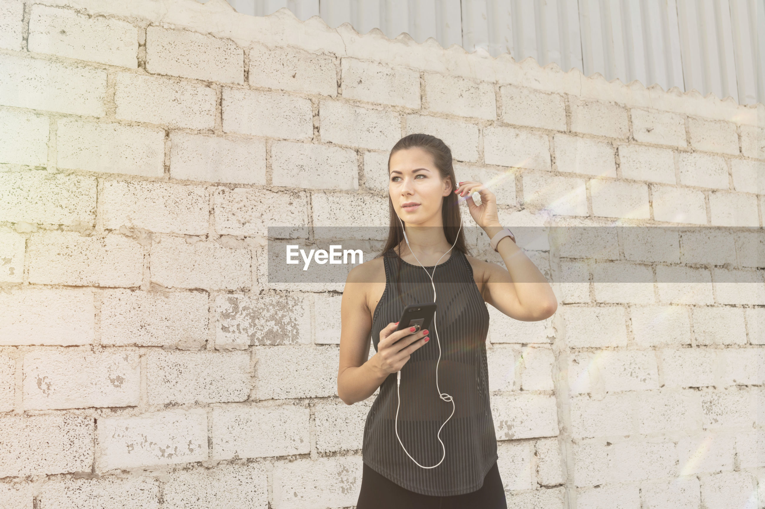 Woman listening music while standing against brick wall