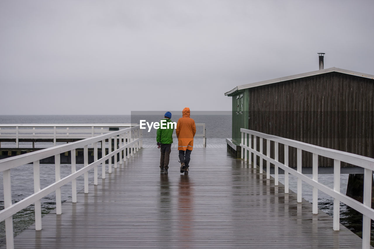 Rear View Of Men Walking On Wet Pier Against Sea And Sky During Rainy Season