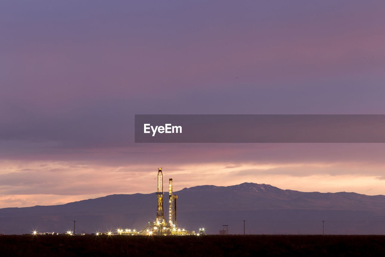 Drilling Rig On Field Against Cloudy Sky