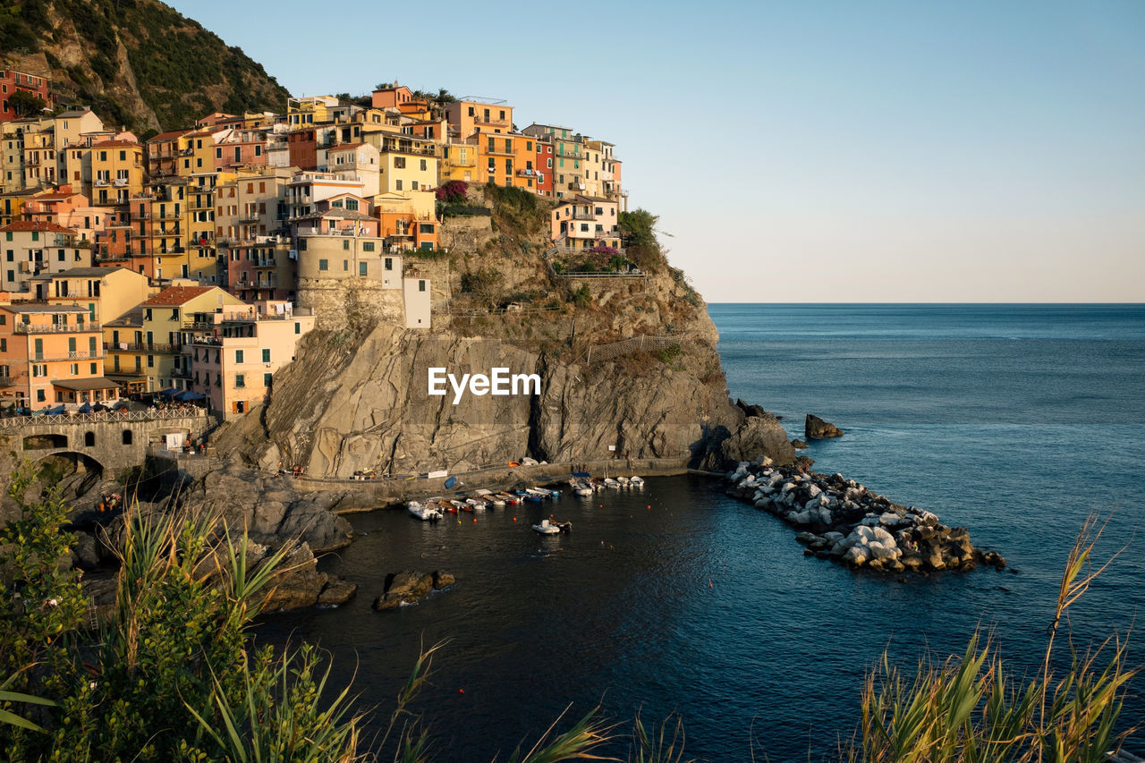 Buildings On Cliff By Sea Against Sky At Manarola