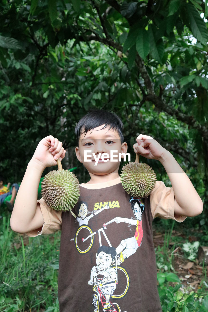 Portrait of smiling boys holding  durian plant