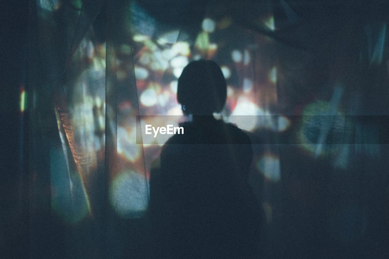 Rear View Of Silhouette Woman Seen Through Curtain At Night