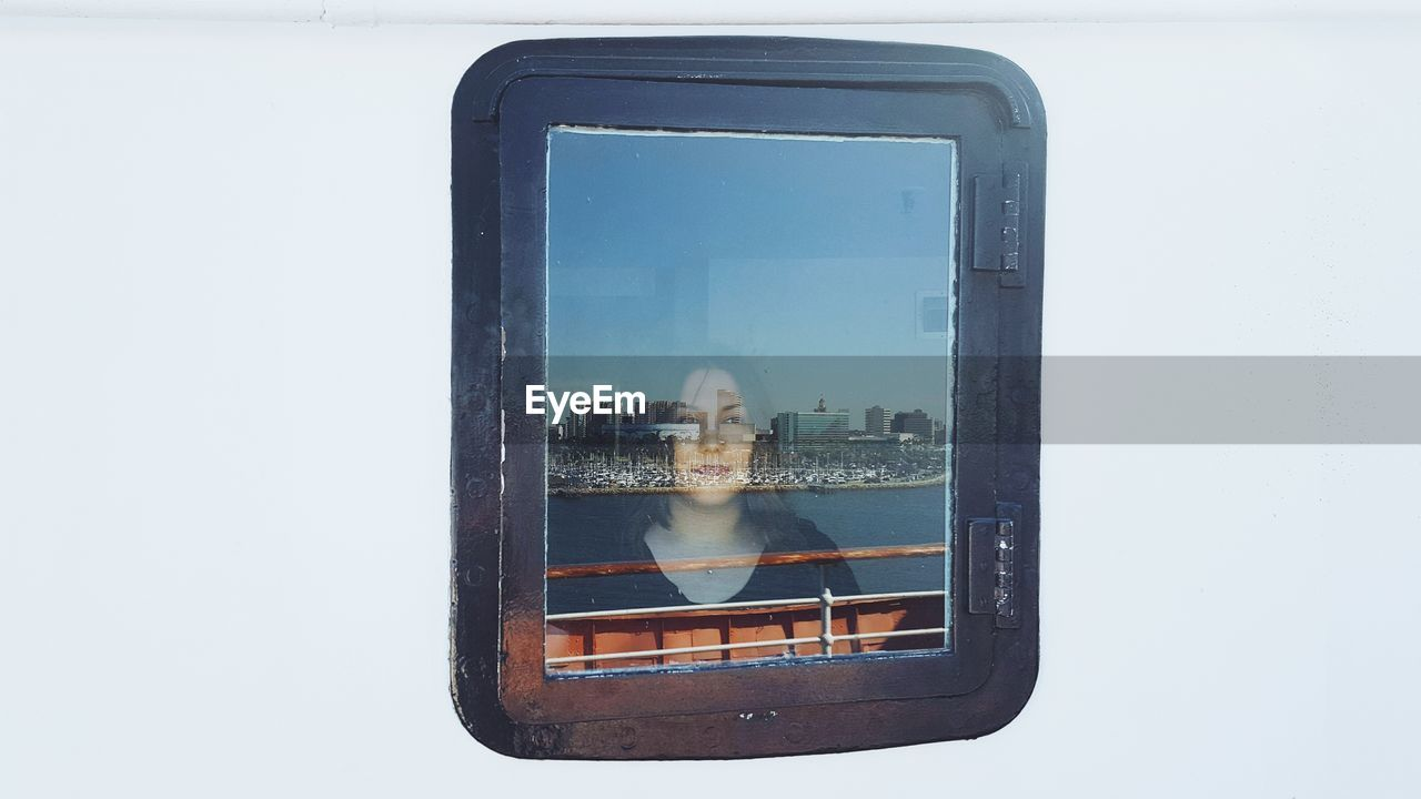 Woman seen through ship window with reflection of city and sea
