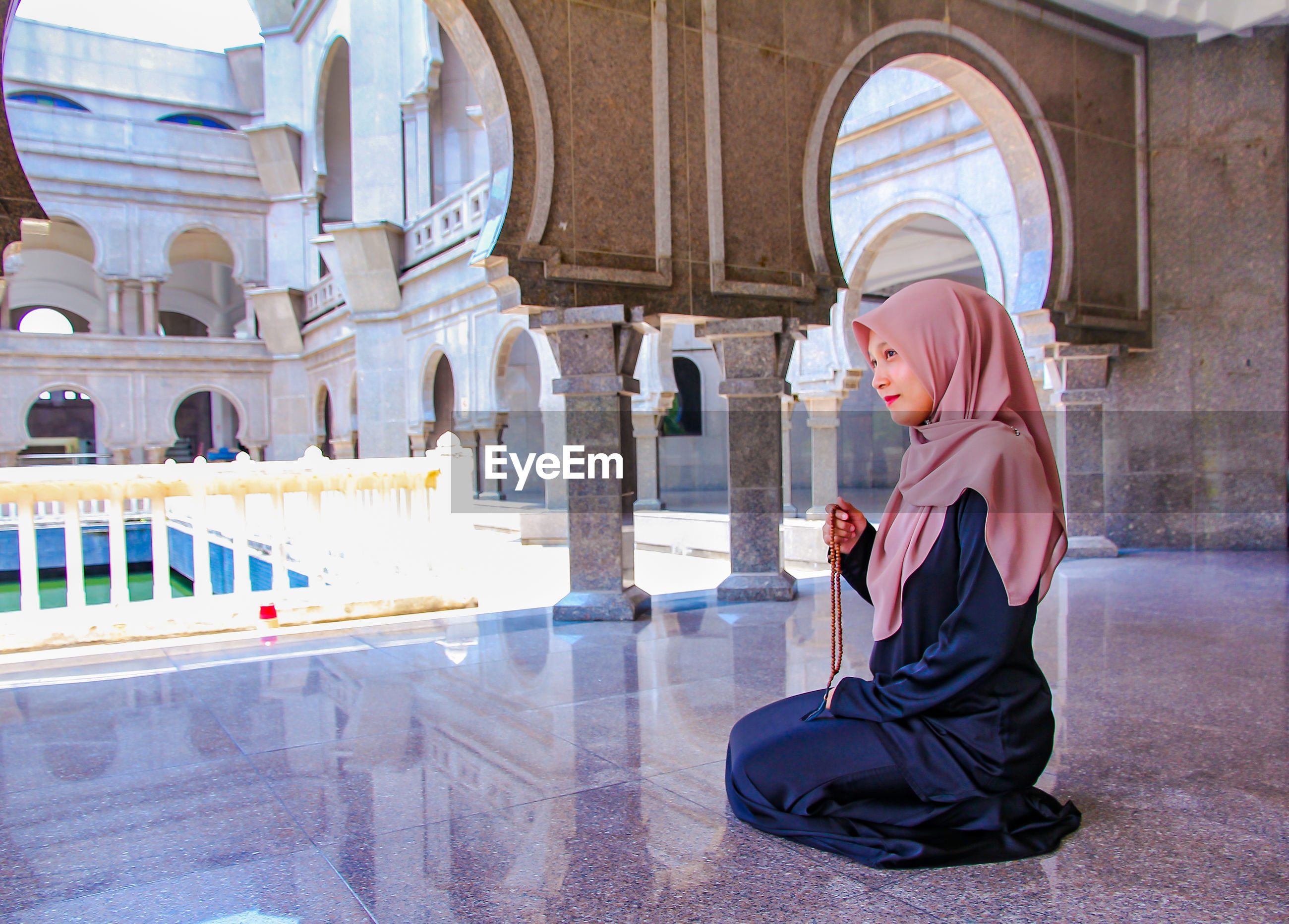 Full length of woman in hijab holding counting rosary beads while praying at mosque