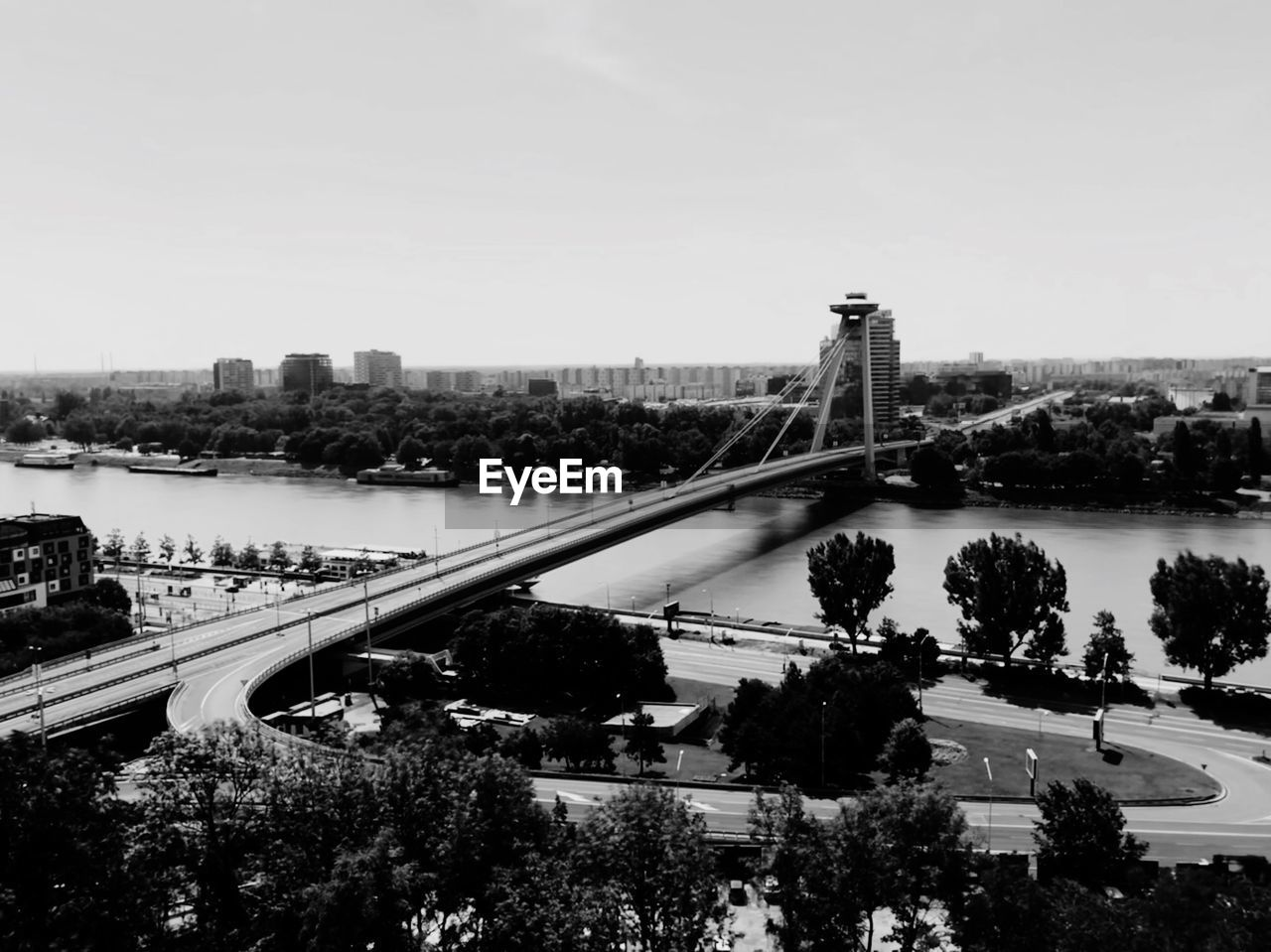 built structure, architecture, building exterior, tree, transportation, bridge, city, connection, sky, bridge - man made structure, high angle view, plant, nature, no people, water, day, river, mode of transportation, cityscape, outdoors, multiple lane highway