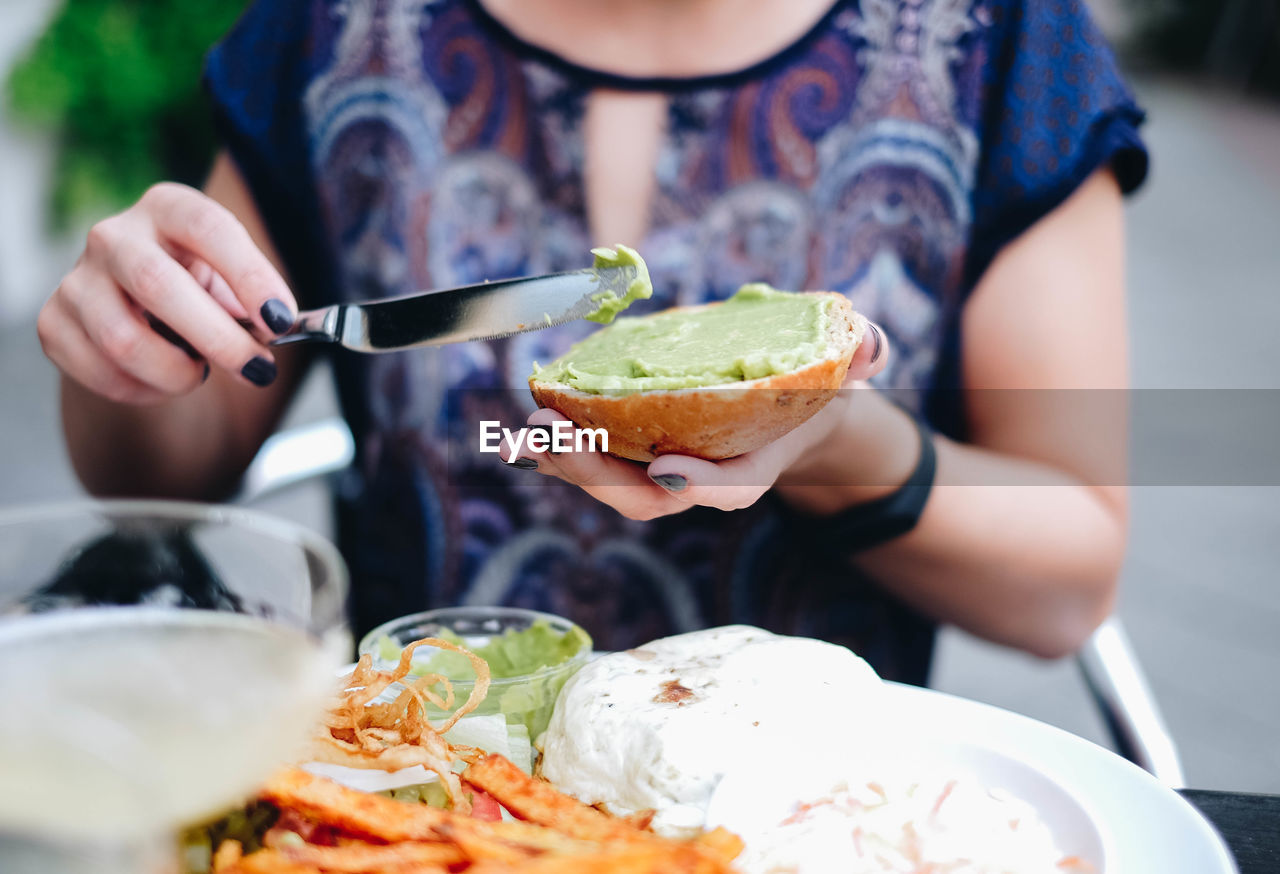 Midsection Of Woman Applying Sauce On Bun In Plate