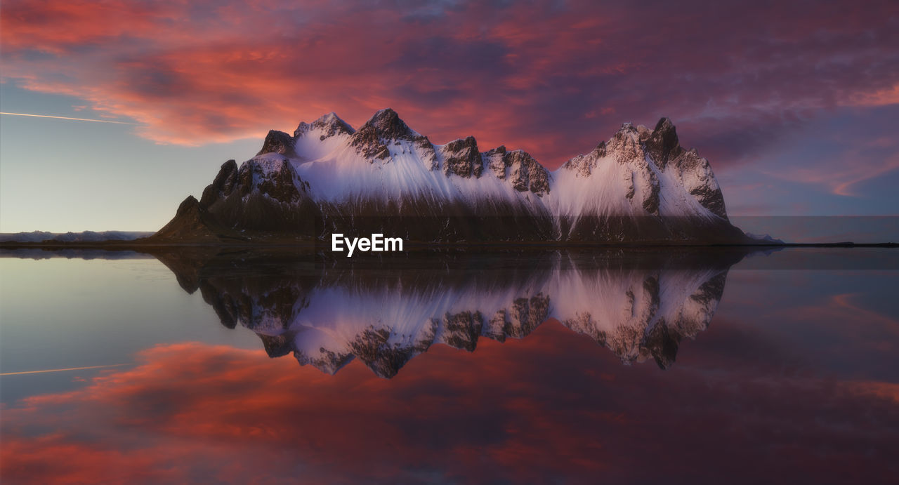 Scenic view of mountains by lake against dramatic sky during sunset