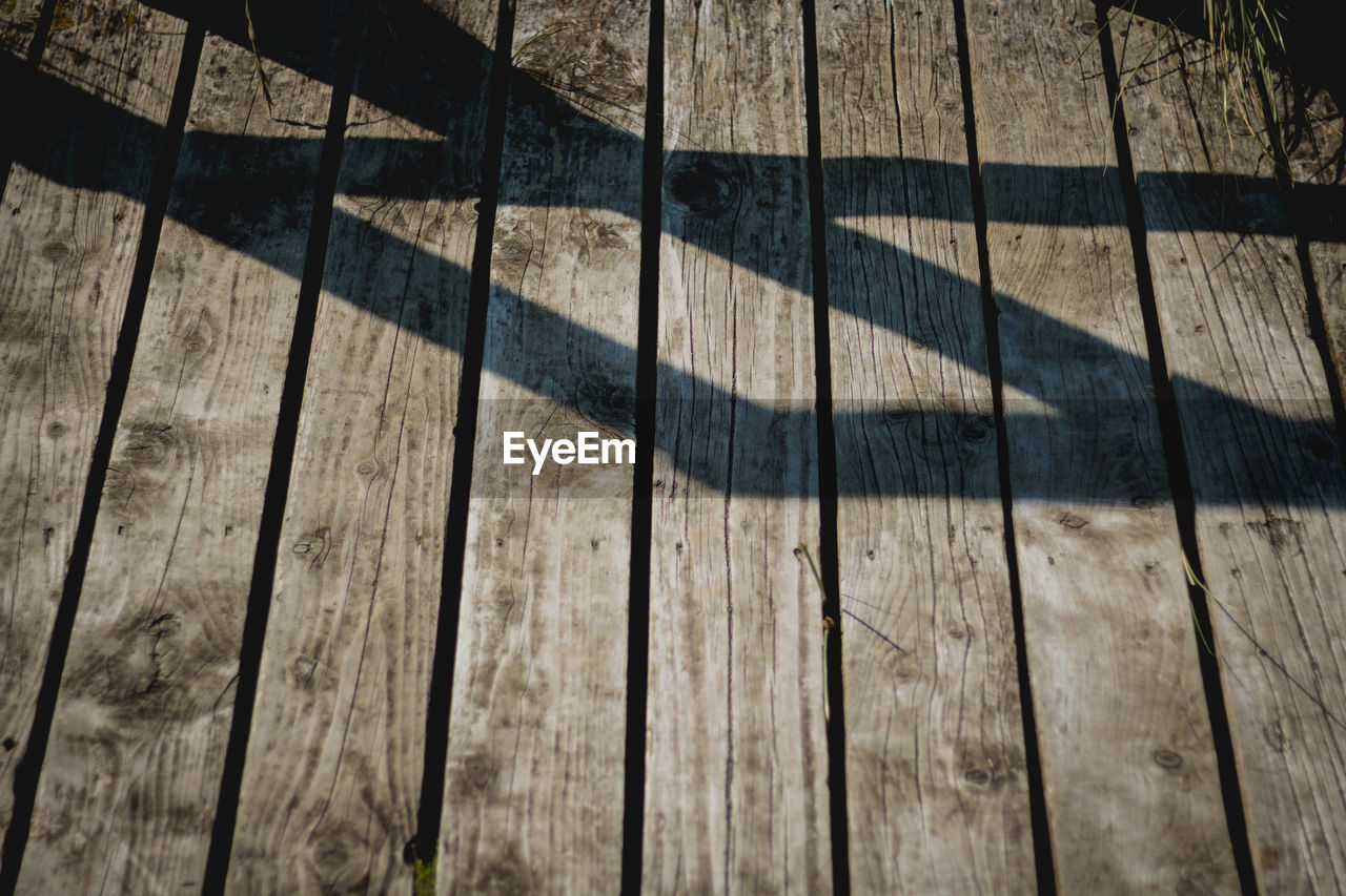 shadow, sunlight, wood - material, pattern, day, no people, high angle view, nature, backgrounds, wood, flooring, full frame, hardwood floor, textured, outdoors, sunny, floorboard, close-up, striped, brown, focus on shadow, wood grain