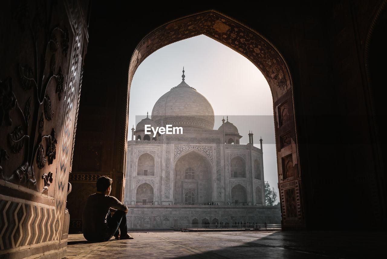 Man Looking At Taj Mahal Through Arch