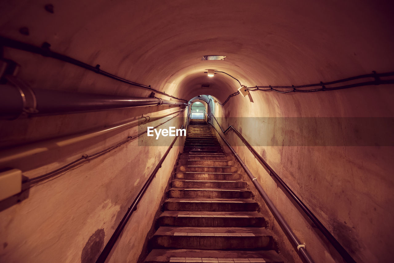 direction, lighting equipment, the way forward, illuminated, architecture, indoors, tunnel, diminishing perspective, railing, built structure, transportation, ceiling, wall - building feature, steps and staircases, no people, light, arch, staircase, low angle view, connection, electricity, light at the end of the tunnel, underground walkway, light fixture