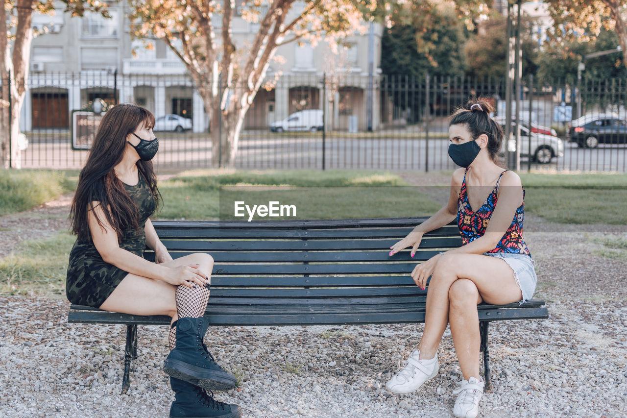 Full length of women wearing mask sitting on bench in park