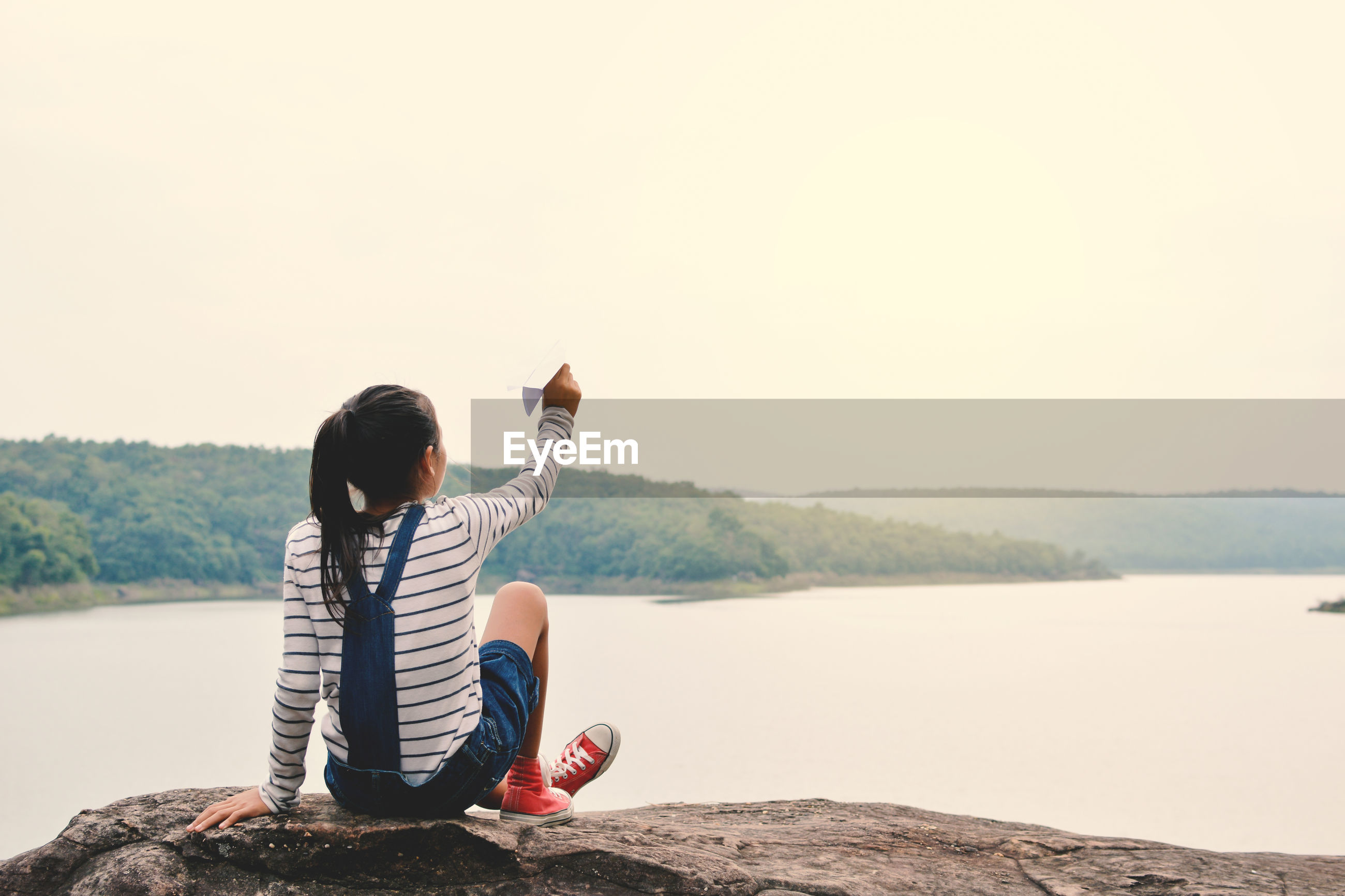 Rear view of girl playing with paper airplane while sitting on rock against lake