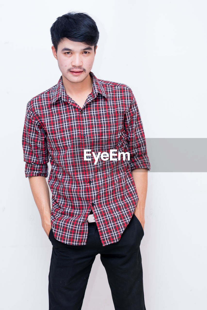 one person, young men, standing, young adult, front view, looking at camera, three quarter length, indoors, casual clothing, studio shot, portrait, white background, hands in pockets, checked pattern, lifestyles, copy space, confidence, teenager