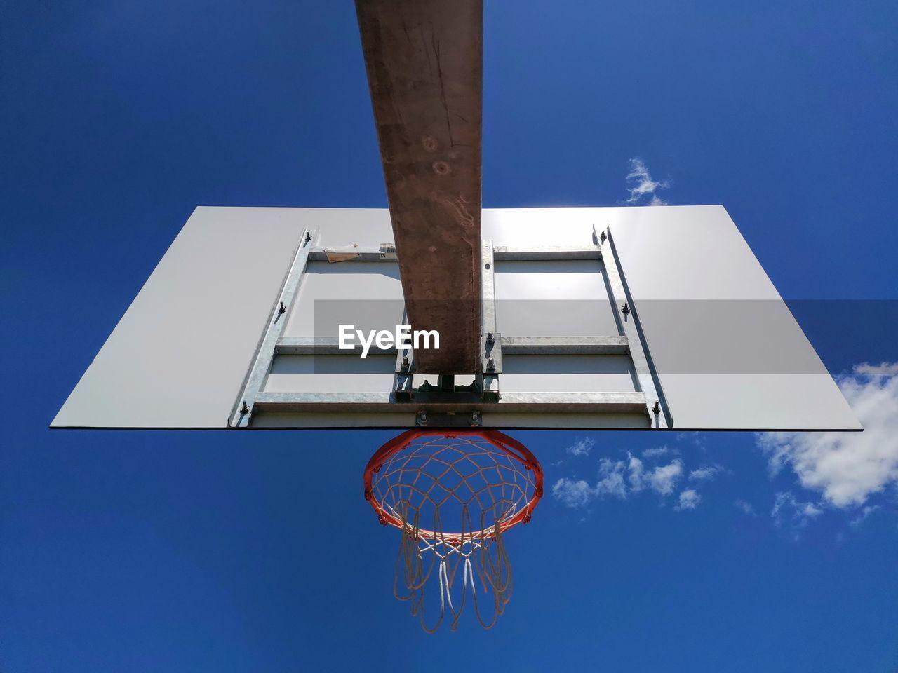 DIRECTLY BELOW SHOT OF BASKETBALL HOOP AGAINST BLUE SKY