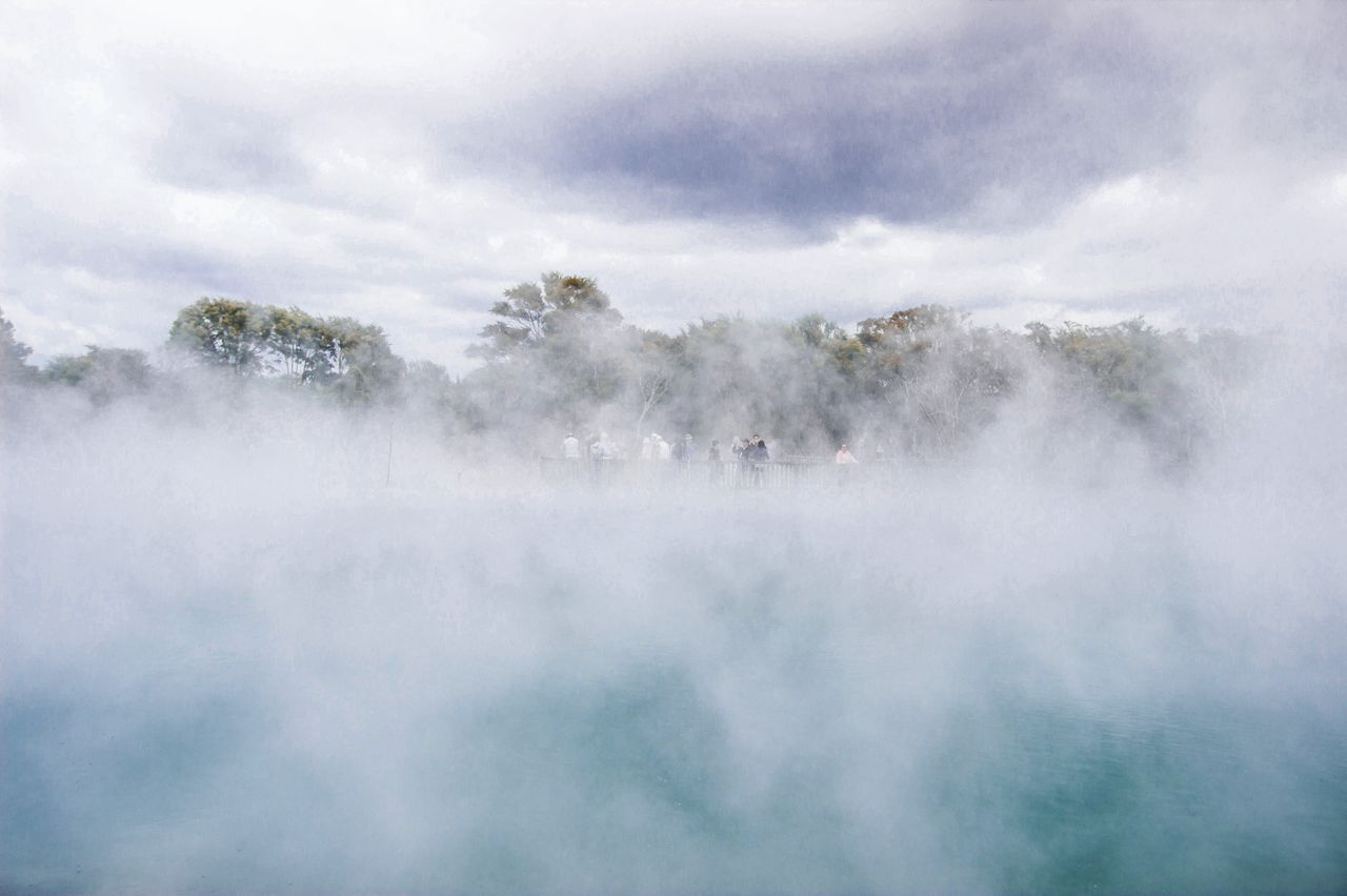 Scenic view of hot spring against cloudy sky during foggy weather