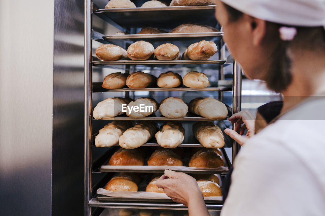 Close-up of woman by food in trays at bakery