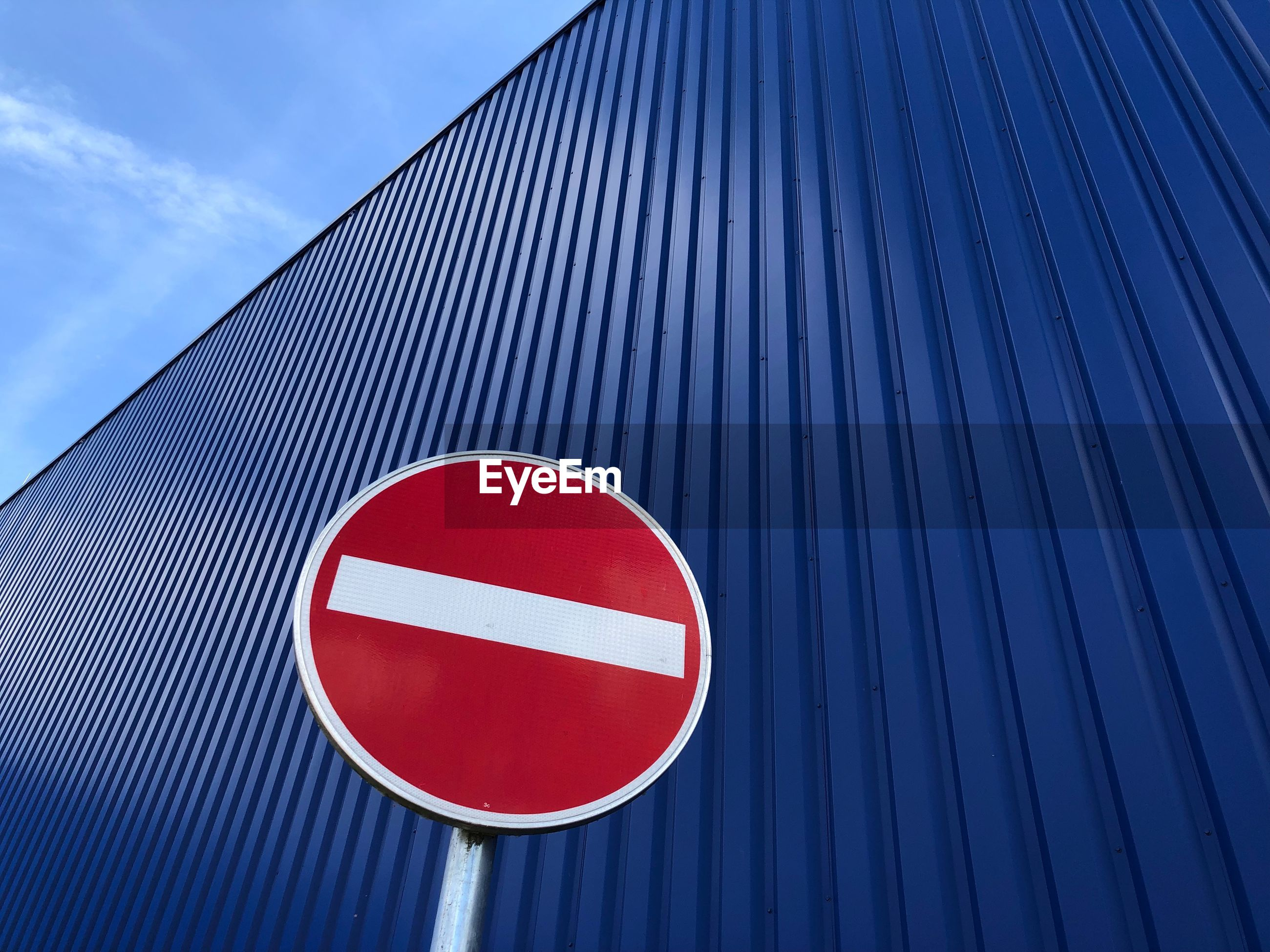Low angle view of road sign against corrugated iron