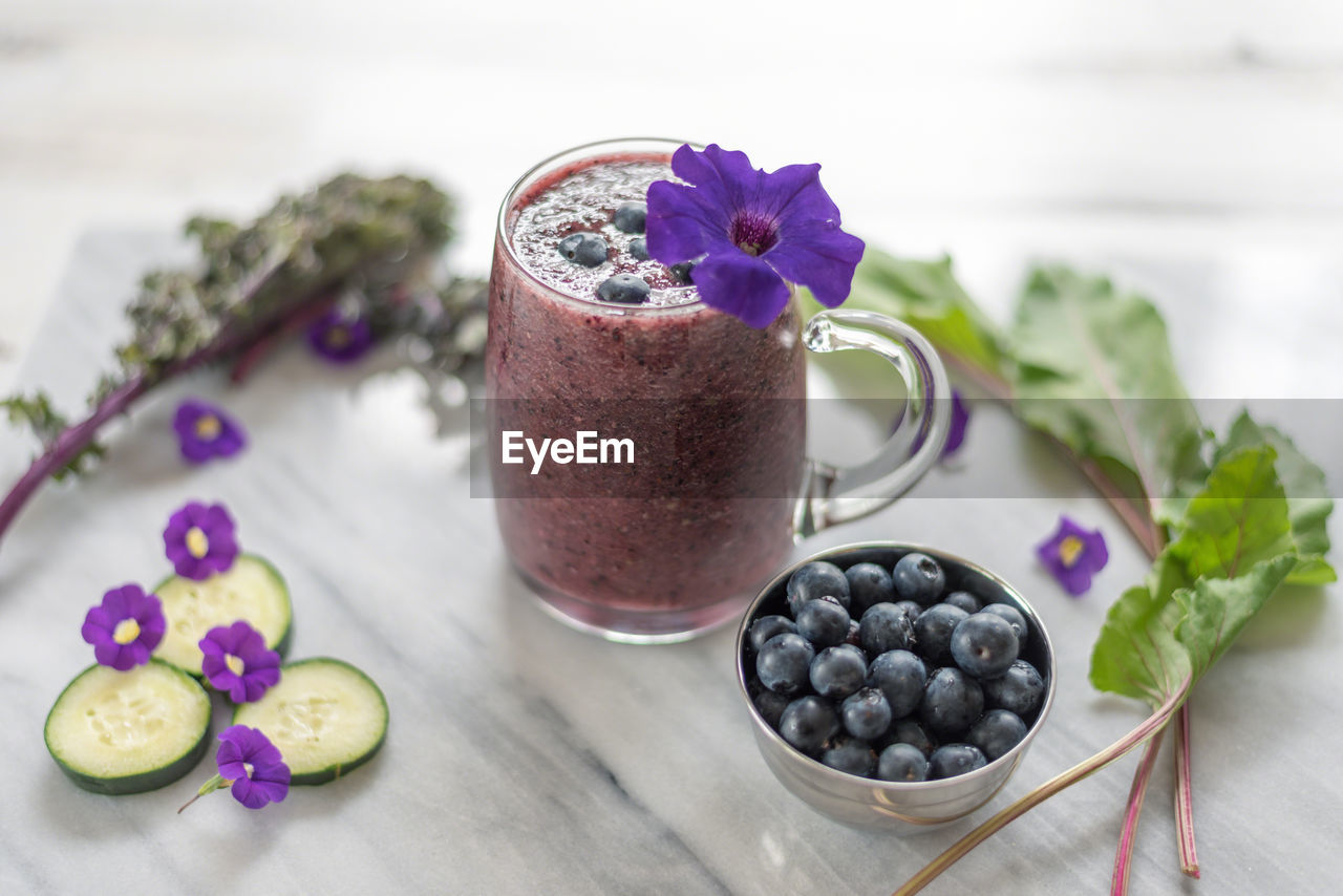 freshness, food and drink, food, healthy eating, wellbeing, table, berry fruit, flowering plant, flower, fruit, blueberry, still life, close-up, no people, indoors, plant, focus on foreground, purple, smoothie, nature, temptation
