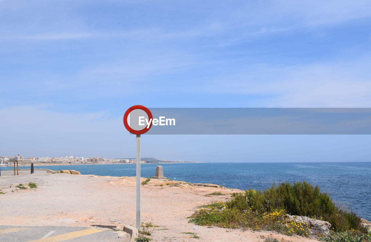 sign, sky, communication, sea, road sign, water, guidance, land, information, scenics - nature, horizon over water, day, information sign, nature, no people, road, beach, blue, horizon, outdoors