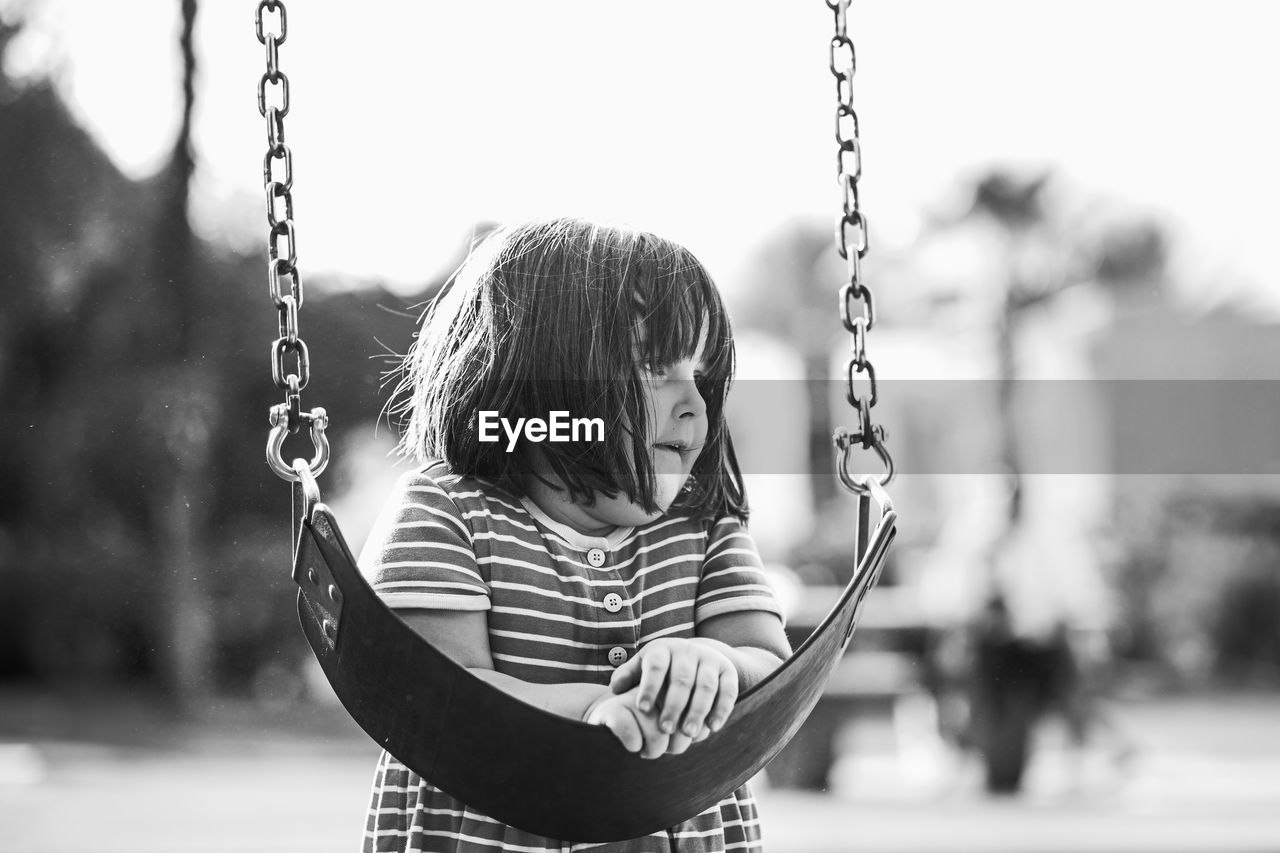 Close-Up Of Girl Leaning On Swing At Playground