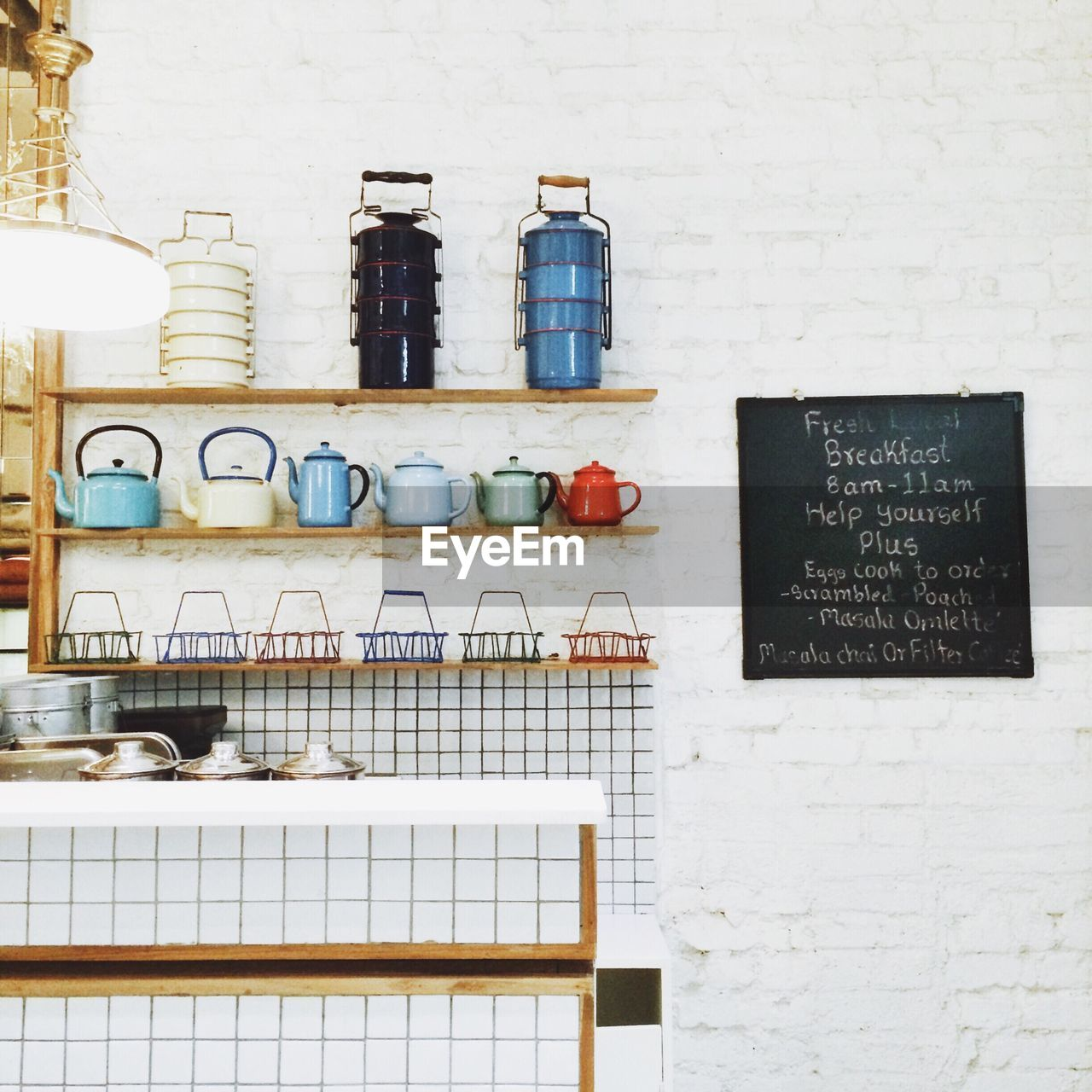 Utensils On Shelf Against Wall With Sign Board