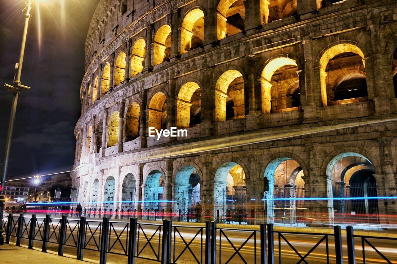 Light trails on street by illuminated coliseum at night