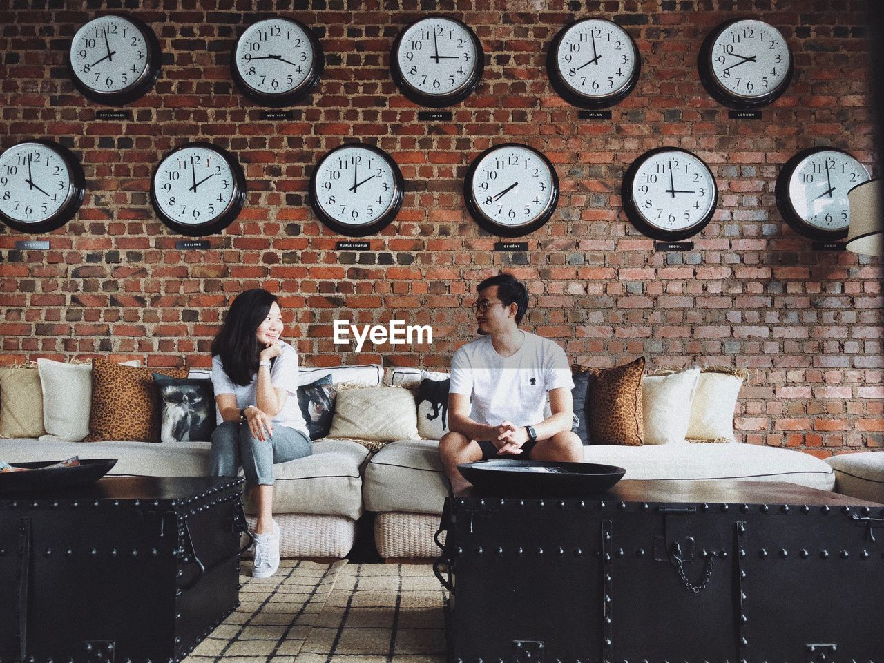 Couple sitting on sofa against wall clocks